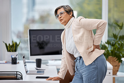 Buy stock photo Shot of a mature businesswoman experiencing back pain while working in an office