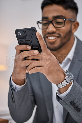 Buy stock photo Shot of a young businessman using a cellphone while working in an office