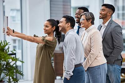 Buy stock photo Shot of a group of businesspeople taking selfies together in an office
