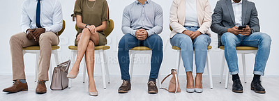 Buy stock photo Studio shot of a group of businesspeople sitting in line against a white background