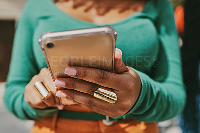 Buy stock photo Shot of an unrecognizable female using a phone in the city