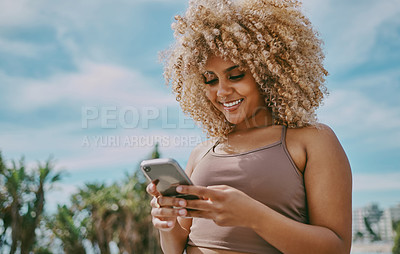 Buy stock photo Shot of a young woman using a phone in the city