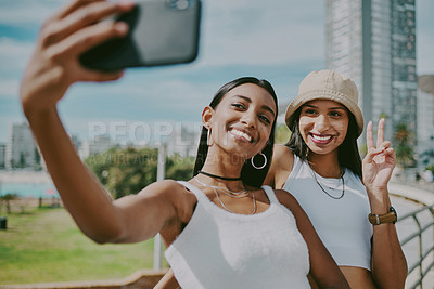 Buy stock photo Shot of two young female friends taking a selfie in the city