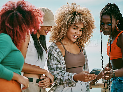 Buy stock photo Shot of a group of young friends using a phone in the city