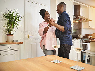 Buy stock photo Shot of an affectionate young couple dancing together at home