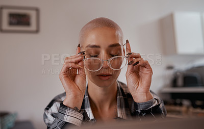 Buy stock photo Shot of a young woman putting on her glasses while sitting at home