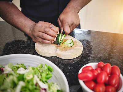 Buy stock photo Closeup shot of an unrecognisable man slicing a cucumber while preparing a salad at home