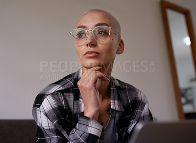 Buy stock photo Shot of a beautiful young woman looking thoughtful while sitting at home