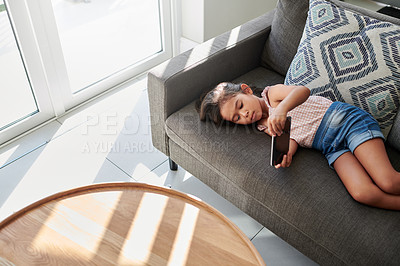 Buy stock photo Shot of a little girl using a phone on the couch at home