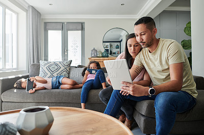 Buy stock photo Shot of a young couple using a digital tablet at home