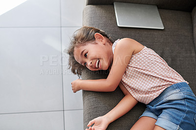 Buy stock photo Shot of a little girl sitting on the couch at home