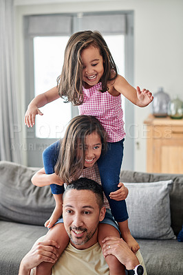 Buy stock photo Shot of a young father spending time with his daughters at home
