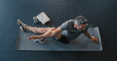 Buy stock photo Shot of a mature man sitting and stretching after working out in the gym alone