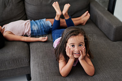 Buy stock photo Shot of two little girls laying on the couch at home