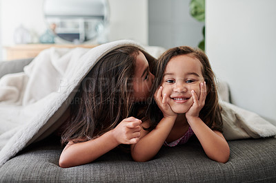 Buy stock photo Shot of a little girl giving her sister a kiss on the couch at home