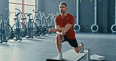 Buy stock photo Shot of a handsome mature man stretching after working out in the gym alone