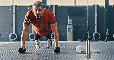 Buy stock photo Shot of a mature man using dumbbells for pushups during his workout in the gym