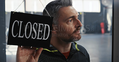 Buy stock photo Shot of a handsome mature trainer turning the sign to the door of his gym