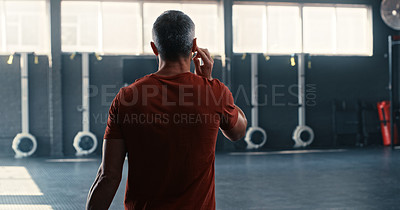 Buy stock photo Shot of an unrecognizable man walking into the gym and getting ready to workout