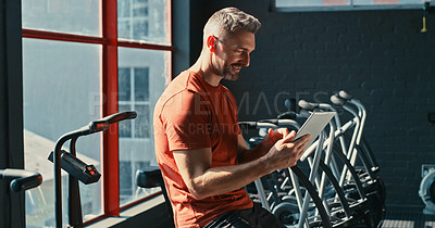Buy stock photo Shot of a handsome mature trainer holding a clipboard and checking the machines in his gym