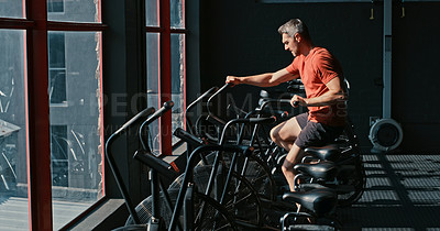Buy stock photo Shot of a mature man working out in the gym alone during the day