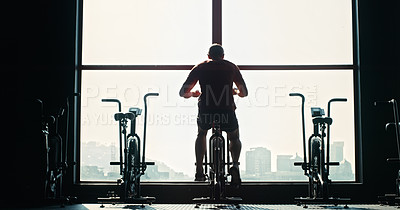 Buy stock photo Shot of an unrecognizable man working out in the gym alone during the day