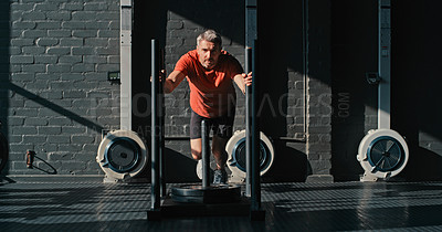 Buy stock photo Shot of a handsome mature man working out in the gym alone during the day