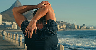Buy stock photo Rearview shot of a mature man stretching his arms while exercising along the promenade