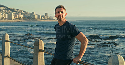 Buy stock photo Shot of a mature man looking thoughtful while exercising along the promenade
